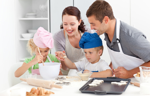 Happy family cooking a cream together in the kitchenの写真素材 [FYI00483321]
