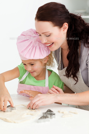 Happy mother and daughter cooking biscuits togetherの写真素材 [FYI00483323]