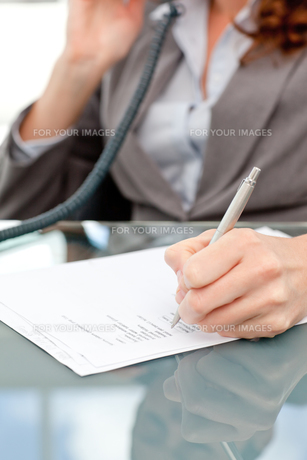 Pretty woman on the phone writing on his notepad in an officeの素材 [FYI00483344]