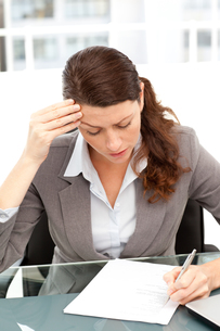Worried businesswoman working at a tableの写真素材 [FYI00483347]