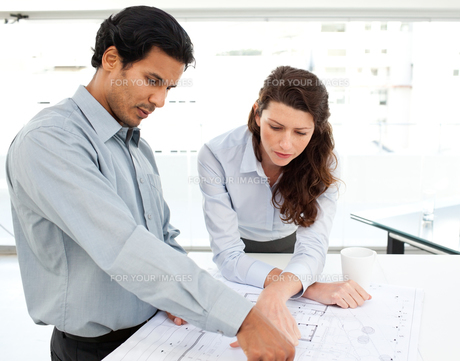 Two serious architects looking at blueprints on a tableの写真素材 [FYI00483358]