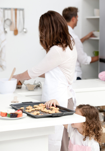 Cute little girl taking cookies while her parents are cookingの写真素材 [FYI00483359]