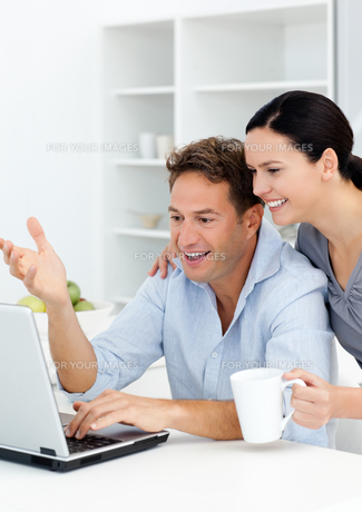 Lovely couple laughing while watching something on the laptop screenの写真素材 [FYI00483361]
