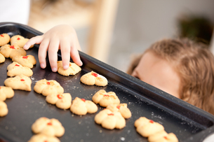 Close up of a little girl taking a cookie behind her motherの写真素材 [FYI00483363]