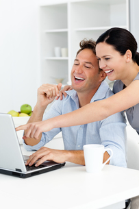Happy woman showing something on the laptop to his boyfriendの写真素材 [FYI00483371]