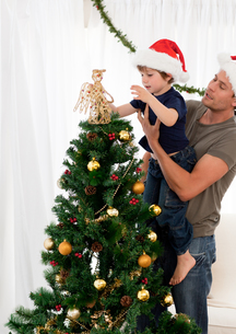 Cute son decorating the christmas tree with his fatherの写真素材 [FYI00483373]