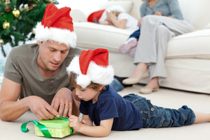Father and son unwrapping a present lying on the floorの素材 [FYI00483374]