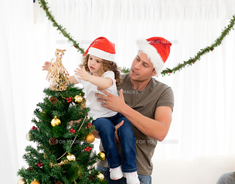 Cute daughter decorating the christmas tree with his fatherの素材 [FYI00483375]