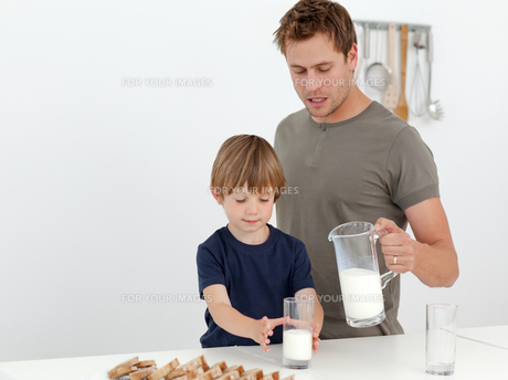 Handsome man giving milk to his sonの素材 [FYI00483376]