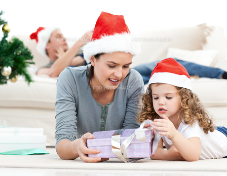 Mother and daughter unwrapping a present lying on the floorの写真素材 [FYI00483377]