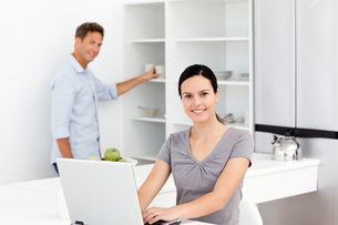 Happy woman working with a laptop while her husband preparing coffeeの写真素材 [FYI00483386]