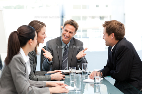 Delighted managertalking to his team at a tableの写真素材 [FYI00483389]