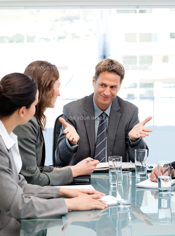 Happy manager talking to his team sitting at a tableの写真素材 [FYI00483390]