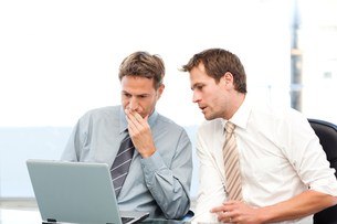 Two concentrated businessmen working together on a laptopの写真素材 [FYI00483401]