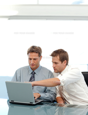 Two partners working together with a laptop sitting at a tableの写真素材 [FYI00483404]