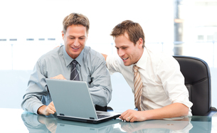 Two happy businessmen working together on a laptop sitting at a tableの写真素材 [FYI00483405]