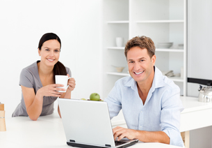 Portrait of a  man working on the laptop while his girlfriend is drinking coffeeの写真素材 [FYI00483408]