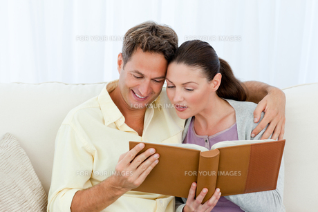 Attentive man and woman looking at a photo album on the sofaの写真素材 [FYI00483409]