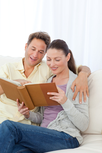 Cute couple looking at a photo album on the sofaの写真素材 [FYI00483411]
