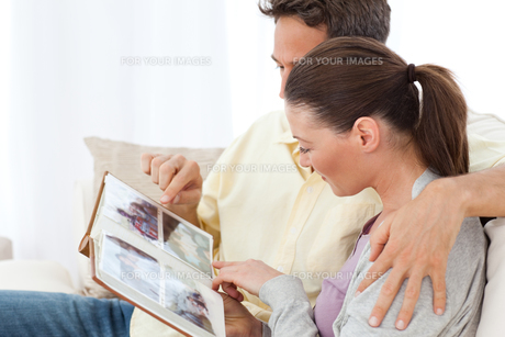 Lovely couple looking at pictures on a photo album on the sofaの写真素材 [FYI00483412]