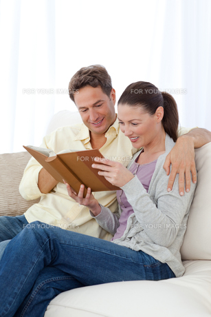 Happy couple looking at pictures on a photo album while relaxingの写真素材 [FYI00483413]