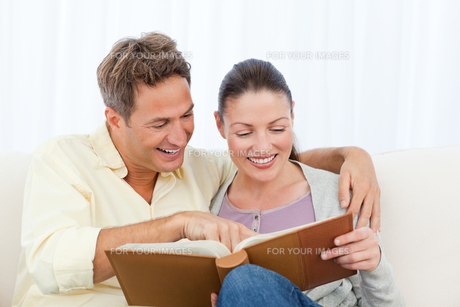Couple smiling while looking at pictures on a photo albumの写真素材 [FYI00483414]