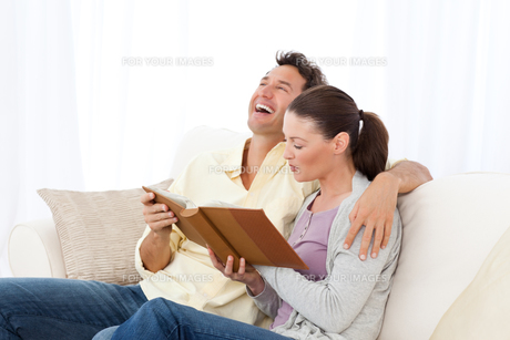 Man laughing while looking at a photo album with his girlfriendの写真素材 [FYI00483415]