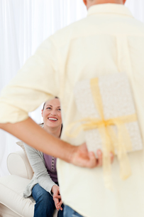 Happy man hiding a present for his girlfriend waiting on the sofaの写真素材 [FYI00483417]