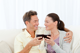 Passionate couple drinking red wine while relaxing on the sofaの写真素材 [FYI00483418]