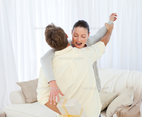 Excited woman catching a present hidden behind her boyfriendの写真素材 [FYI00483419]