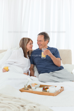 Lovely couple having breakfast in their bedの写真素材 [FYI00483437]