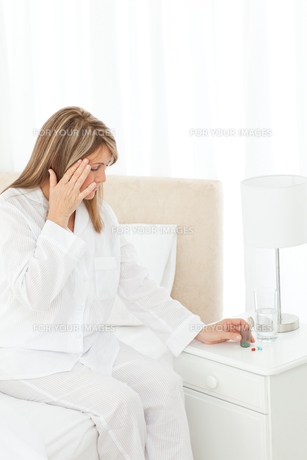 Woman having a headache on her bedの素材 [FYI00483438]