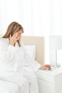 Woman having a headache on her bedの写真素材 [FYI00483438]