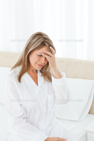 Woman having a headache on her bedの写真素材 [FYI00483439]