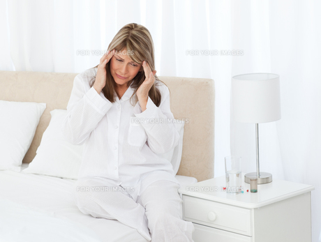 Woman having a headache on her bedの写真素材 [FYI00483441]