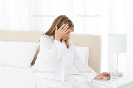Woman having a headache on her bedの写真素材 [FYI00483442]