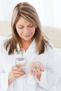 Sick woman taking her pills at homeの写真素材 [FYI00483443]