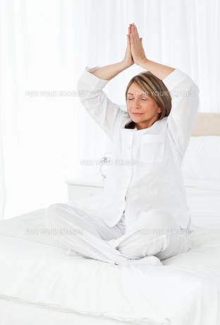 Senior practicing yoga on her bedの写真素材 [FYI00483447]