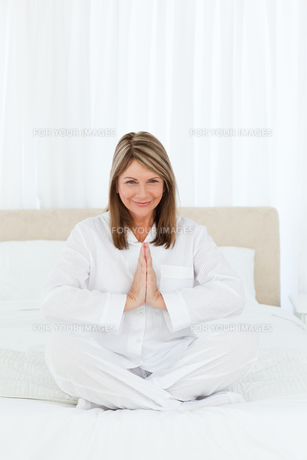 Senior practicing yoga on her bedの写真素材 [FYI00483448]