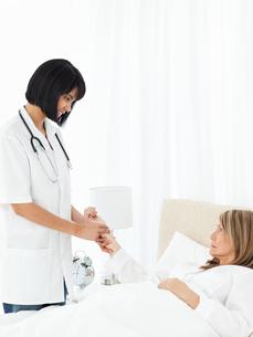 Nurse taking the pulse of her patientの写真素材 [FYI00483449]