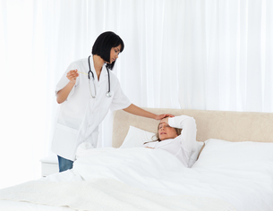 Nurse taking the temperature of  her patientの写真素材 [FYI00483453]