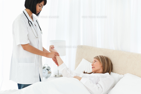 Nurse taking the pulse of her patientの写真素材 [FYI00483454]