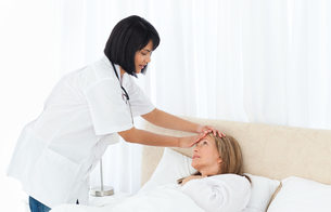 Nurse taking the temperature of  her patientの写真素材 [FYI00483455]