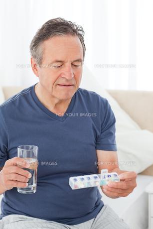 Sick man taking his pillsの素材 [FYI00483457]