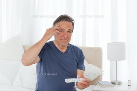 Sick man taking his pillsの素材 [FYI00483462]