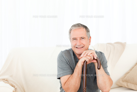 Happy mature man with his walking stick on his bedの素材 [FYI00483464]