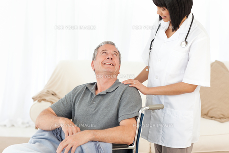 Man in his wheelchair with his nurse at homeの写真素材 [FYI00483470]