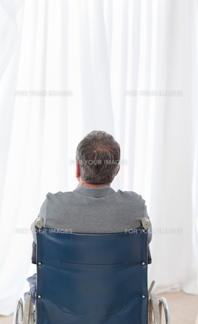 Mature man in his wheelchair with his back to the cameraの素材 [FYI00483480]