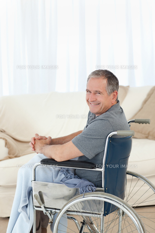 Mature man in his wheelchair looking at the cameraの素材 [FYI00483486]