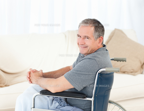 Mature man in his wheelchair looking at the cameraの素材 [FYI00483487]